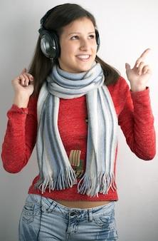 灰色の背景にヘッドフォンを持つ美しさの若い女性