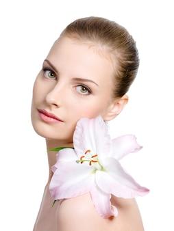 Bellezza di giovane donna con il giglio su una spalla - isolata su bianco