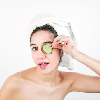 Beauty young woman with wrapped towel around head holding cucumber slice over her eyes