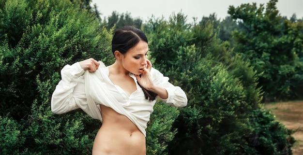 Концепция красоты, молодости и сексуальности. молодая обнаженная женщина наслаждается природой среди растений в саду. сельский роман