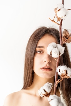 Beauty and youth concept. beautiful woman in cozy clothes holding branch of cotton flowers