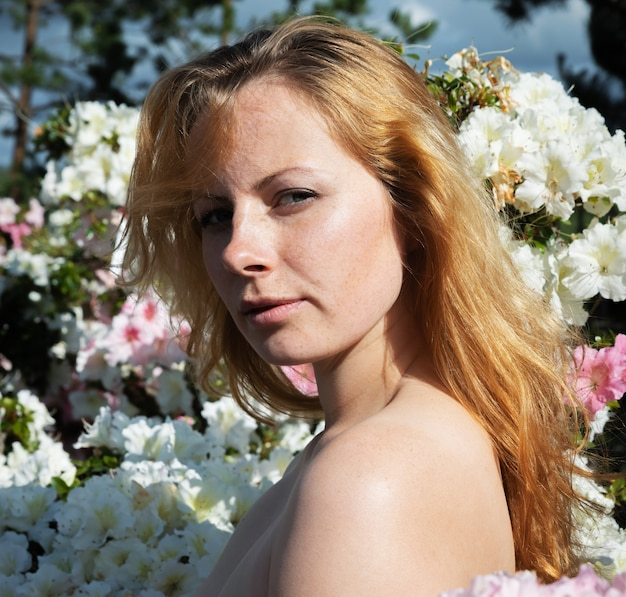 Beauty and youth concept. portrait of a beautiful blonde nude young woman among the flowers of azalea