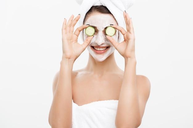 ビューティーユーススキンケアコンセプト-ポートレート美しい白人女性はクリームを適用し、彼女の顔の前に新鮮なキュウリを保持します。白い壁の上に隔離されます。