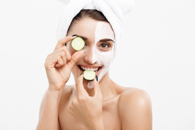 Beauty youth skin care concept - portrait beautiful caucasian woman apply cream and holding fresh cucumber in front of her face.isolated over white wall.