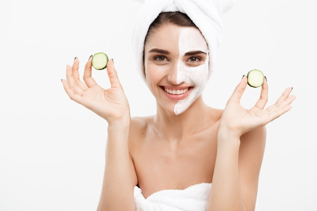 Beauty youth skin care concept - portrait caucasian woman applying cream and holding fresh cucumber in front of her face .isolated over white.