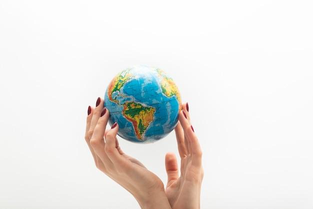 Красивая женская рука держит глобус. мир в руках человека. белая поверхность.
