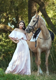 Beautyful woman in dress with horse
