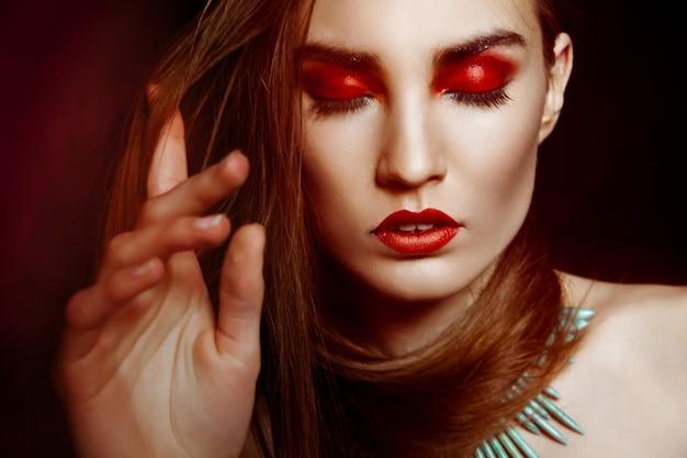 어둠 위에 창의적인 화장을 한 아름다운 여성