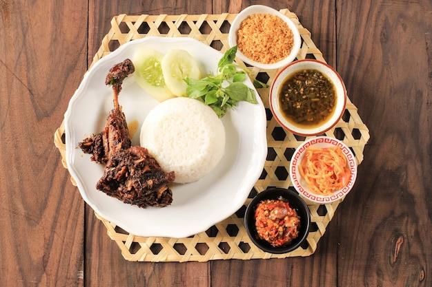 Bebek madura、インドネシアの伝統的な揚げ鴨メニュー。人気のメニューは東ジャワのマドゥラから来ました。通常、生野菜とスパイシーなサンバルを添えて。ペニエタンとして人気