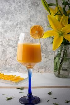 Bebida de naranjaconアルコールservidaen una copa de cristal