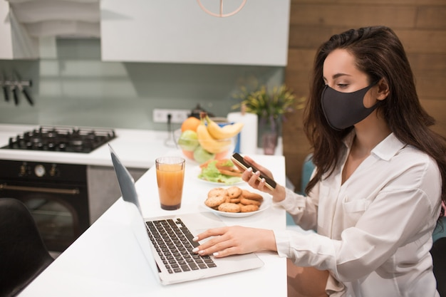 Because of the coronavirus pandemic, a woman in isolation at home. she works at home, is wearing a mask and has a video conference on her laptop.