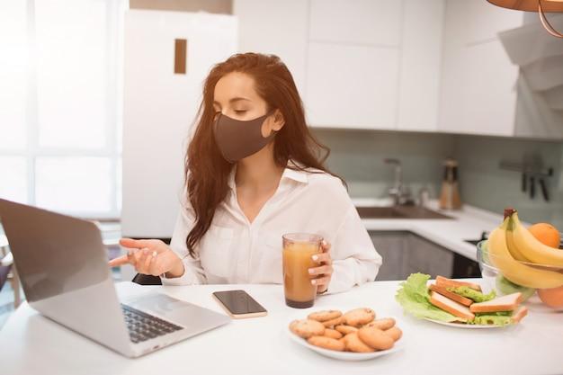 코로나 바이러스 전염병 때문에 집에서 고립 된 여성. 그녀는 집에서 일하고 마스크를 쓰고 노트북에서 화상 회의를합니다.
