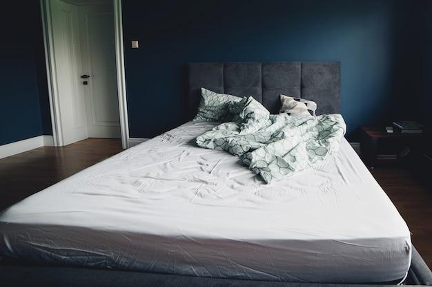 自宅の寝室のベッド。朝の時間に空のベッド。