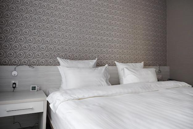 현대적인 침실 호텔의 침대, 깨끗한 베개 및 침대 시트.