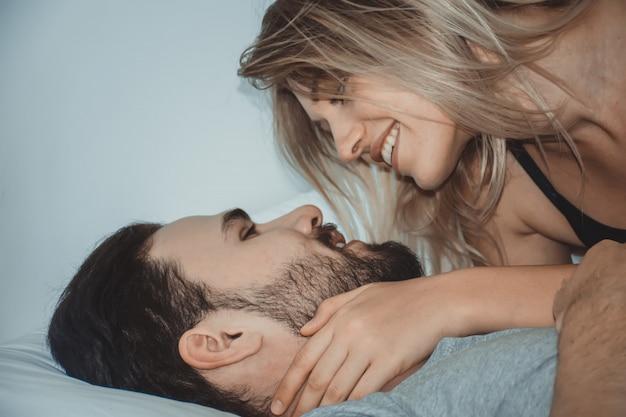 愛情のあるカップルが一緒にベッドで横になっているbed.happyカップルでキスします。