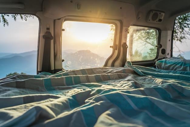 Кровать в мини-автофургоне, припаркованном среди удивительного горного пейзажа.