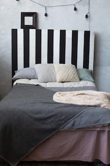クラシックなスタイルのグレーと白の色の縞模様の枕とリビングルームのベッド