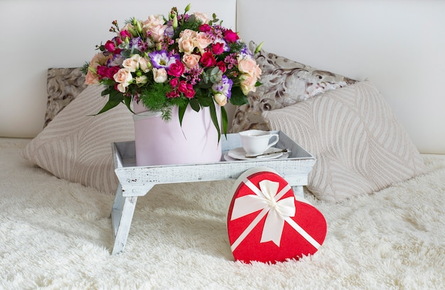 On the bed is a small table with flowers, a cup of tea and a gift