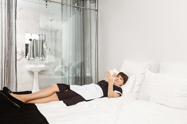 Bed is so soft and comfortable. portrait of housemaid violating rules and lying on bedroom in hotel room, browsing or watching videos with smartphone instead of cleaning apartment of client