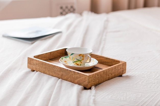 On the bed is a wooden tray with a cup and coffee. photo