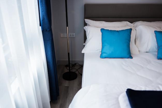 Постельное бельё с чистыми белыми узорными подушками и простынями в комнате красоты.