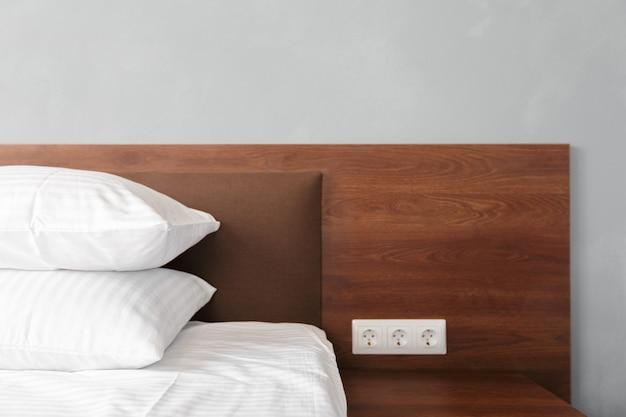 뷰티 룸에서 깨끗한 흰색 베개와 침대 시트로 침대 메이드-업.