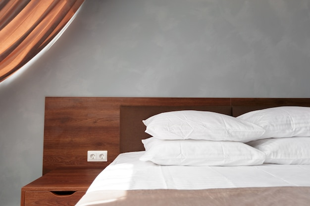 Bed maid-up with clean white pillows and bed sheets in beauty room.