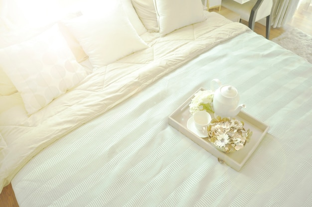 Bed maid-up with clean white pillows and bed sheets in luxury room.
