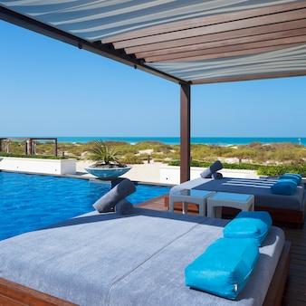 수영장과 해변 근처에 침대.