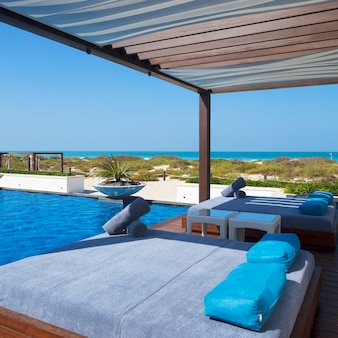 Bed near swimming pool and beach.