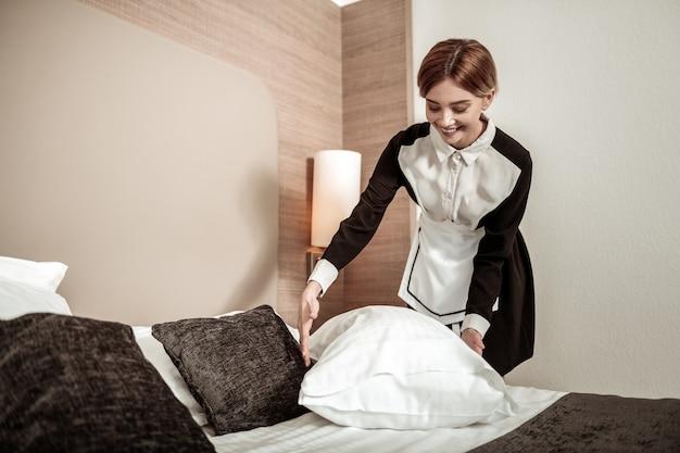 クライアントのベッド。クライアントのベッドを作りながら笑っているプロのブロンドの髪のホテルのメイド
