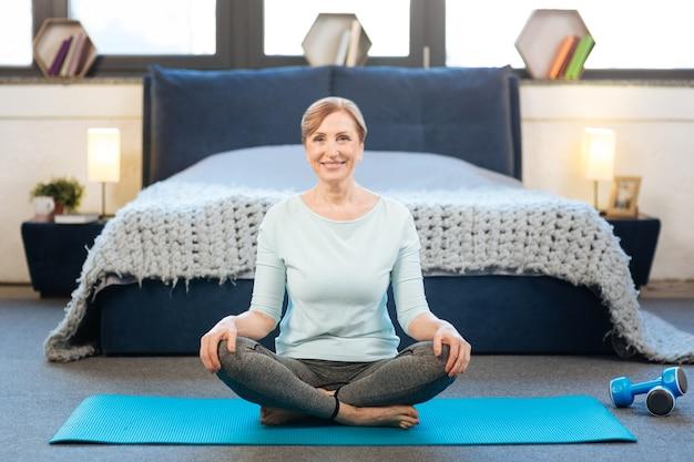 背景のベッド。床に座って自宅でヨガのトレーニングをしている広い笑顔で晴れやかな楽しい女性