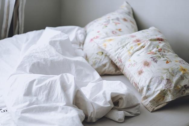 Кровать с белым одеялом и подушками по утрам. домашний комфорт