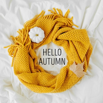 黄色のニットスカーフ付きのベッド。居心地の良い背景。秋のコンセプト。