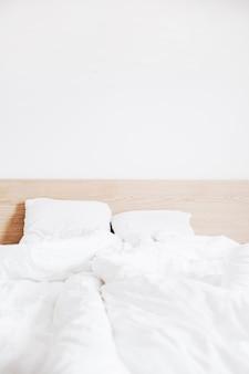 깨끗한 흰색 리넨과 흰색 벽이있는 침대