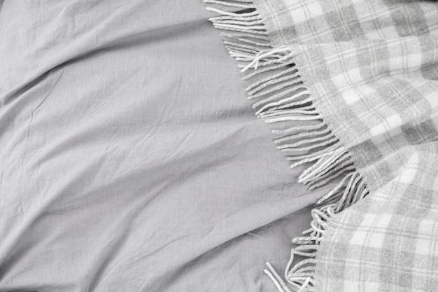 Кровать с серым шерстяным пледом или одеялом и серым постельным бельем.