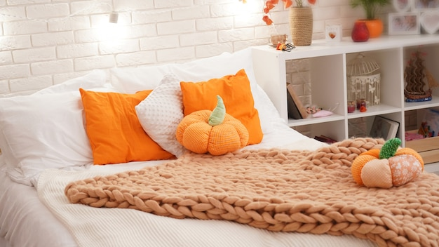 Bed with light bed linen covered with a knitted blanket of coarse yarn. in the bedroom on the bed are pumpkin textiles.