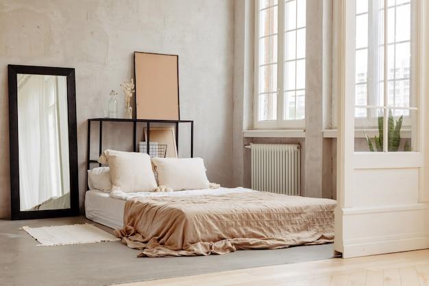 Кровать с подушками и красивым постельным бельем теплых тонов.