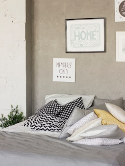 Bed with pillows in room in the loft. Concrete walls, posters. Scandinavian interior