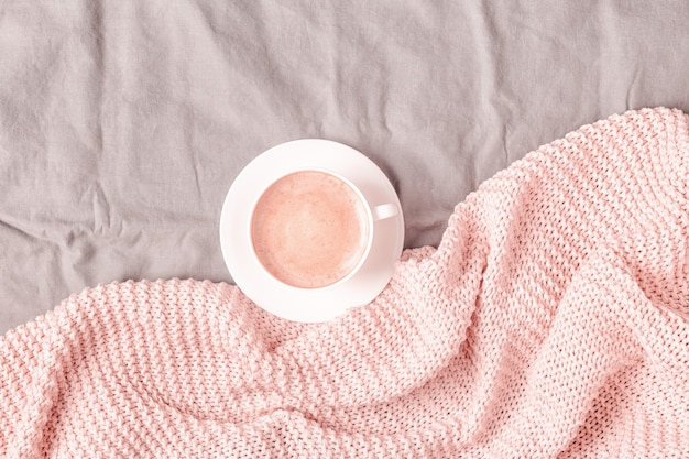 Кровать с розовым вязанным пледом и кофе