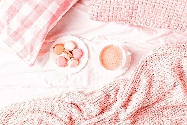 Кровать с розовым вязаным пледом, кофе и миндальным печеньем, вид сверху, копировальное пространство, плоская планировка.