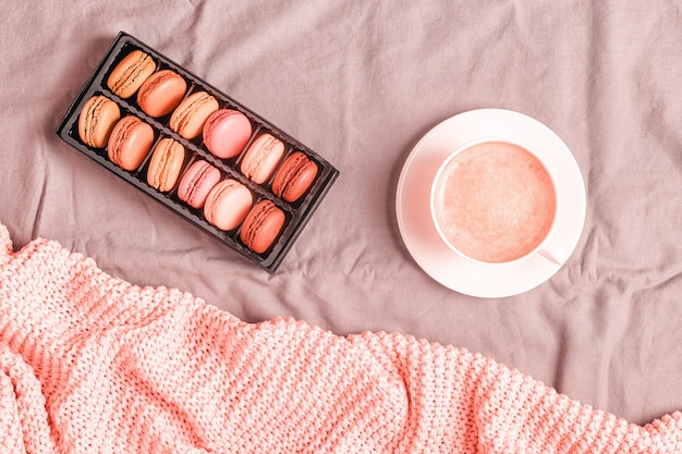 분홍색 니트 격자 무늬, 커피, 마카롱이 있는 침대, 위쪽 전망, 복사 공간, 평평한 누워.