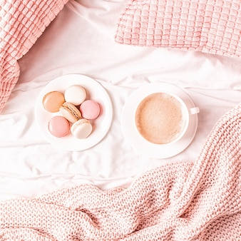Кровать с розовым вязанным пледом, кофе и макарунами