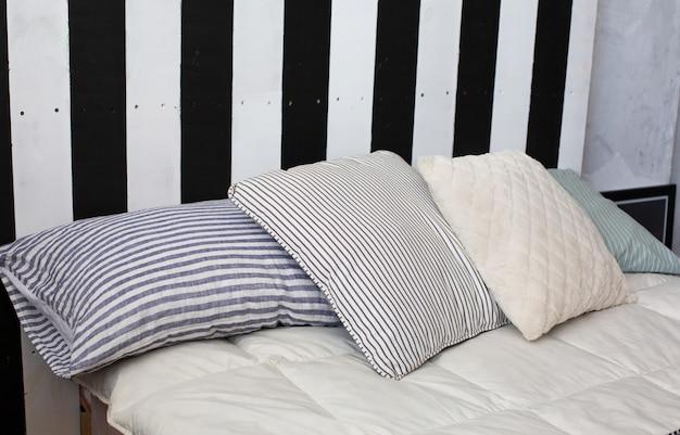 クラシックなスタイルのグレーのストライプの枕が付いたベッド。クローズアップショット