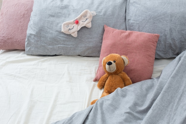Bed with teddy bear on gray linens