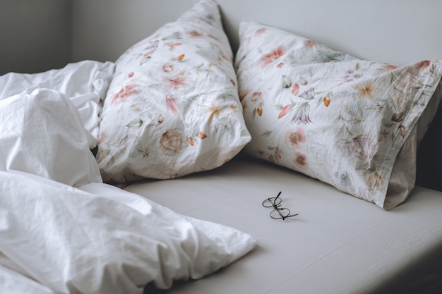 Bed with a white blanket and pillows in the morning. home comfort