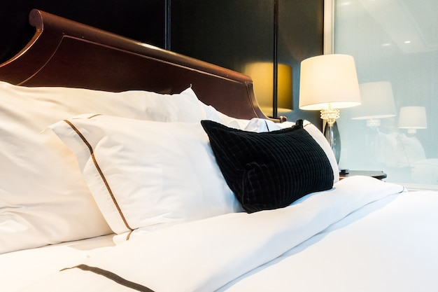 Bed with white duvet and black cushion