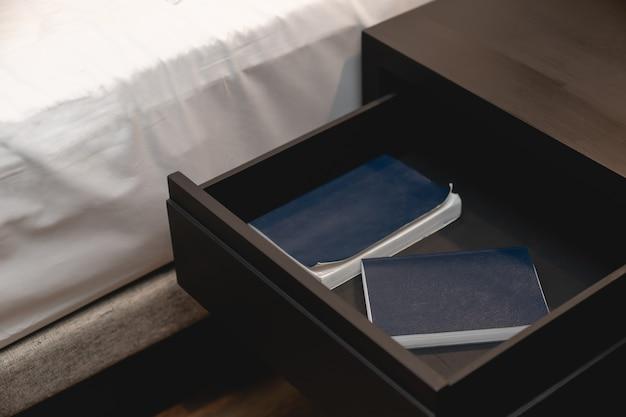 흰색 시트가 있는 침대와 나무 서랍 스탠드 옆, 내부에 있는 노트 책.