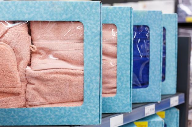 Постельное белье разных цветов в упаковке на полках в магазине крупным планом