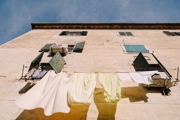 寝具は、ペラストモンテネグロの窓の間のロープで乾かされます